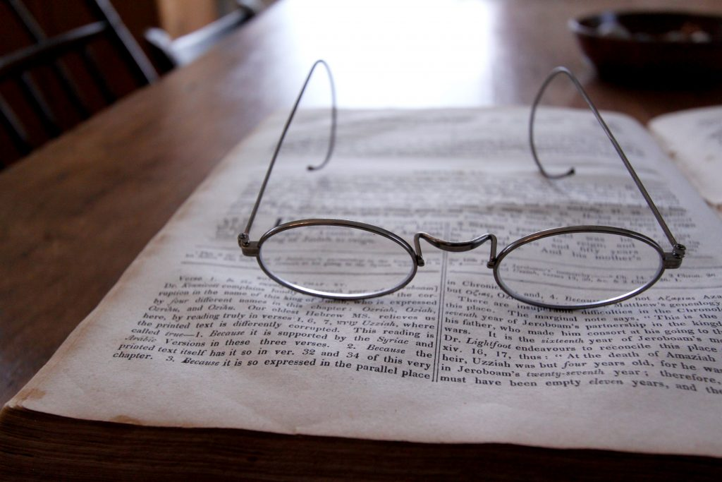 A pair of glasses sits on an open bible on a table.