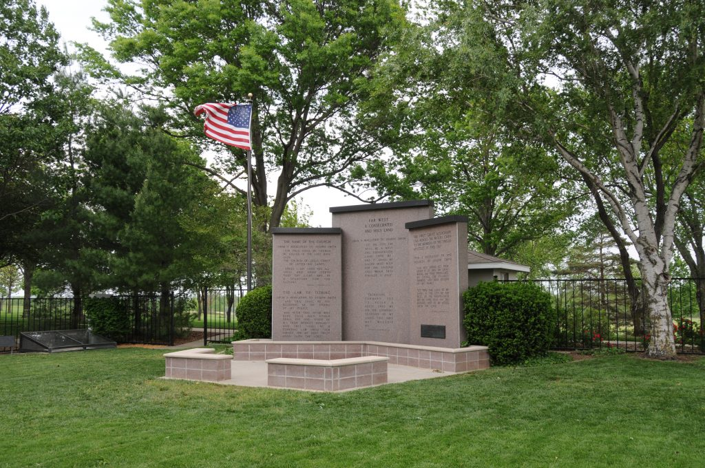 "A set of three large, granite memorials stand close together on a concrete pad. Next to them is a flagpole with an American flag flying on it. Behind the memorials are trees, bushes, a simple metal fence, a path and a small building. The middle memorial has at its top the words ""Far West A Consecrated and Holy Land"""