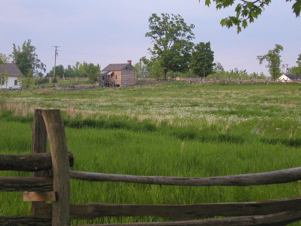 A brown-gray log home from across a fenced field.
