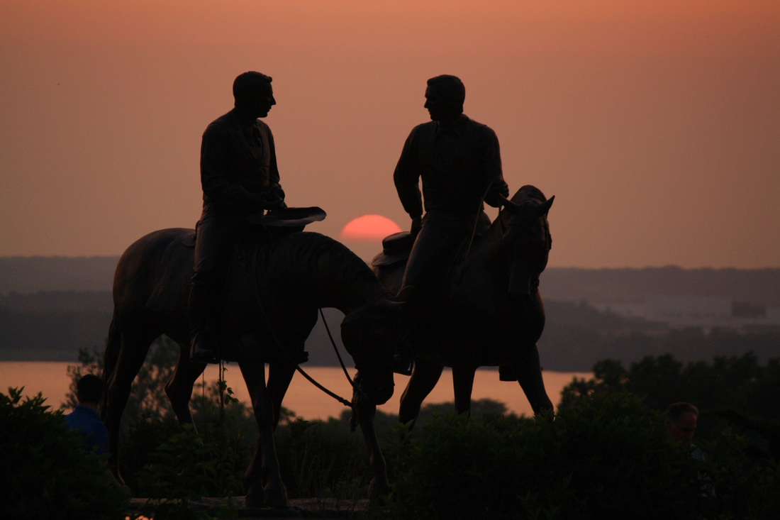 A silhouette of a statue of Joseph and Hyrum on horses. Visible in the background are trees, a river, trees on the opposite shore, and an orange sunset. The whole photo, including the river, is tinted in orange because of the sun.