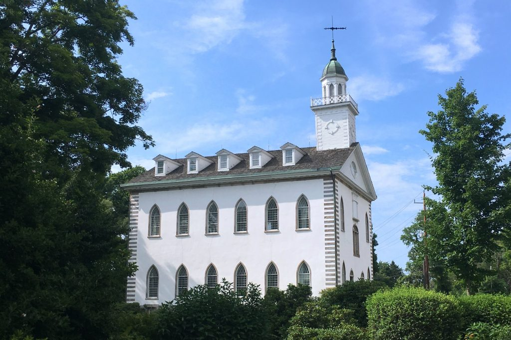 The Kirtland Temple, a white building with two stories and a garret and bell tower, is seen from across a lawn, bushes and trees.