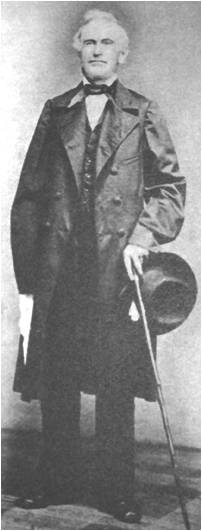 David Whitmer stands, holding a cane and hat, wearing a long coat, white shirt, and dark trousers, vest and tie.