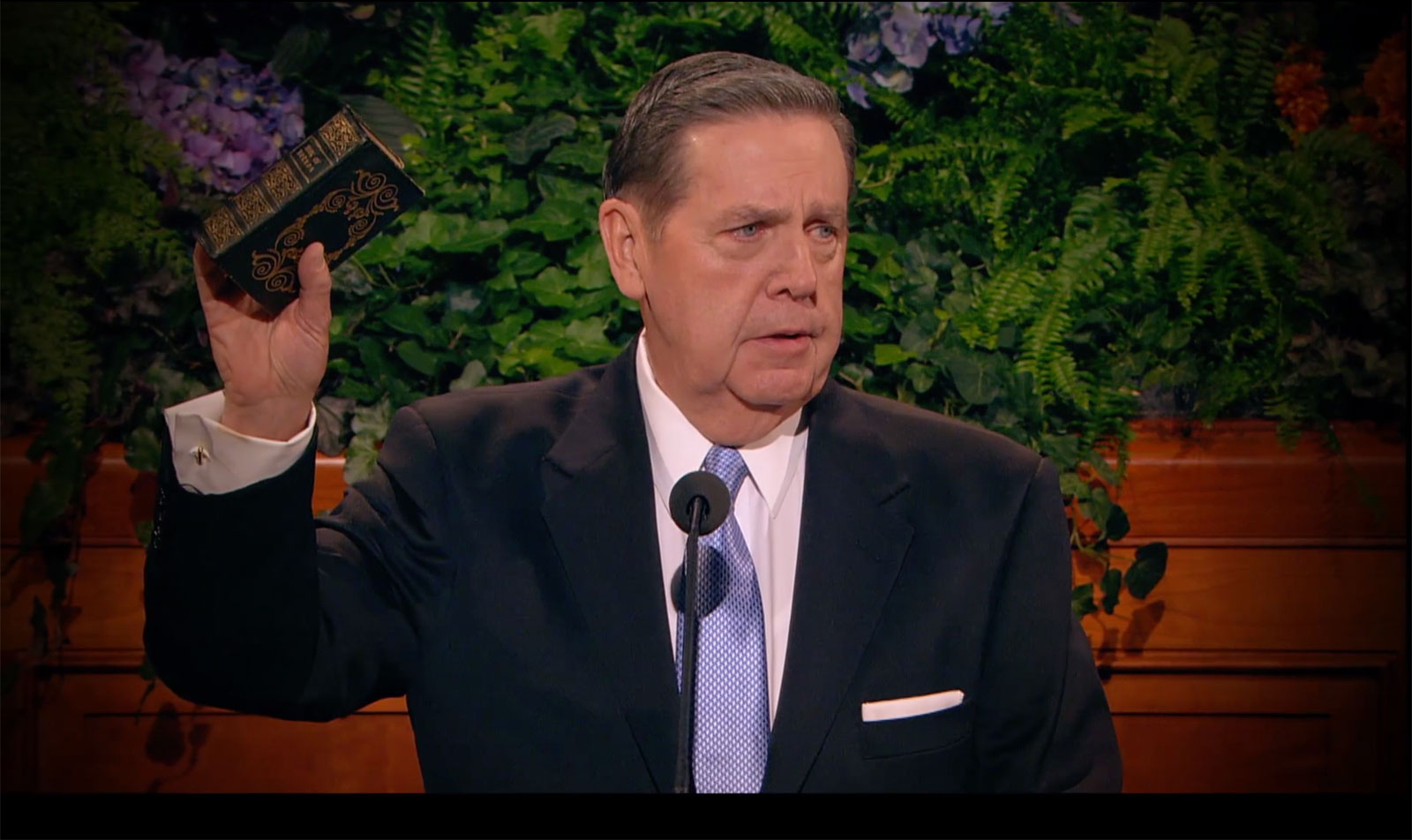 Jeffrey R. Holland, in a black suit, white shirt and light blue tie, stands at the pulpit in the conference center and holds up a copy of The Book of Mormon once owned by Hyrum Smith.