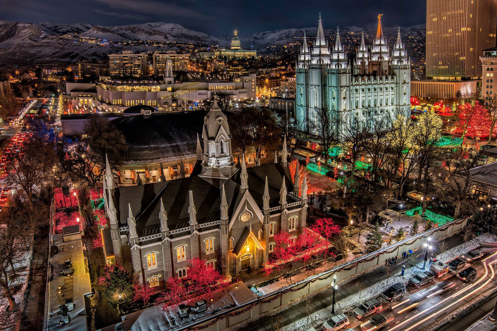 An image of Temple Square at Christmas. In the foreground is the chapel on temple square, and in the background is the temple. All around in the trees and bushes are bright Christmas lights. Other Salt Lake City building are visible in the background behind the temple.