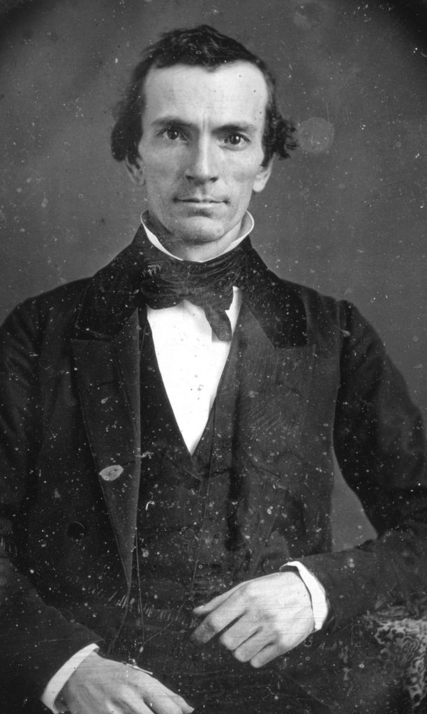 Daguerreotype Oliver Cowdery stands in a suit, vest, and tie. His expression is neutral