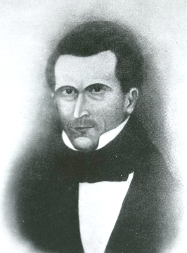 A portrait of George Miller created with dark crayon. He wears a dark coat and cravat and a white shirt with the collar up. There appears to be a little stubble around his mouth. He has a sharp nose and a full head of dark hair.