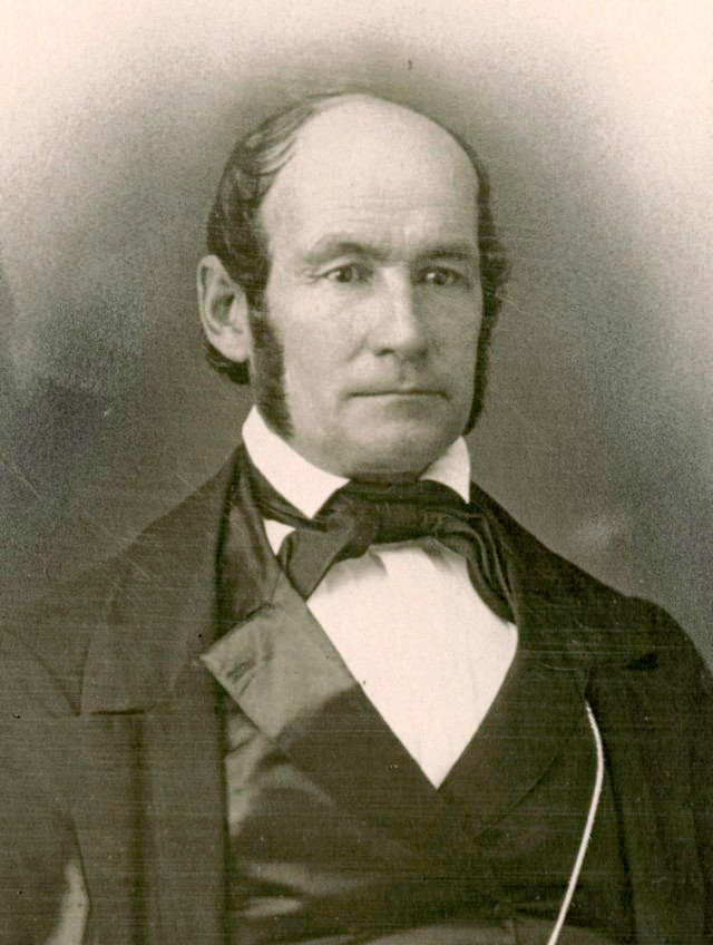 A daguerrotype of Heber C. Kimball. He wears a dark vest, a darker coat and tie, and a white shirt. He has a neutral expression and sideburns that come down to his jawline. He is balding. He has dark hair and eyes.