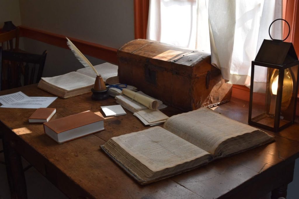 On a table underneath a window is a Bible on each end, a small book, a stack of papers, a stack of envelopes with names on them, a small chest, a quill in an inkwell, and a lantern. Light streams in through the window over the items on the table