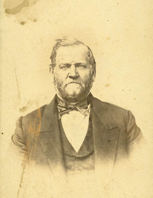 A sepia image of Orson Hyde. He has a short beard and mustache and appears to have salt-and-pepper hair. He wears a dark coat and vest, a white shirt, and a midtone cravat.