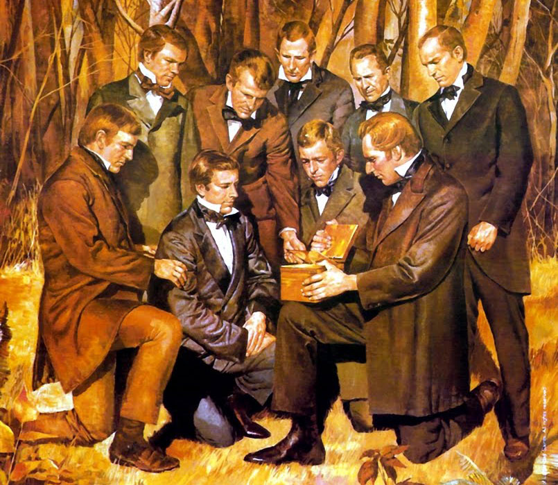 A painting. Joseph Smith, Jr. kneels with one knee on the ground, holding the golden plates on his other knee. Three men kneel close to him, looking at the plates, and five other men surround them, looking at the plates.