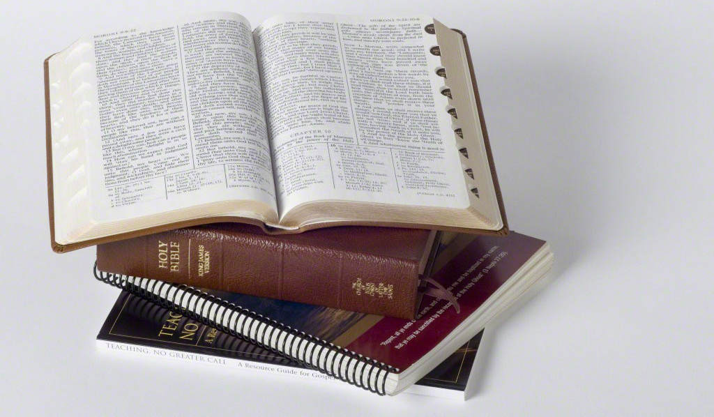 A set of scriptures sits on top of a two manuals. The top book of scriptures is open toward the viewer.