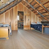 Two rooms divided by a wall make up an upstairs area directly beneath the log home's roof. Two beds sit in one room.